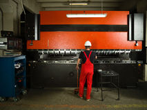 Helmet operating an industrial machinery. Back side view of a worker, standing, wearing red overalls, and a white protective helmet operating an industrial Royalty Free Stock Image