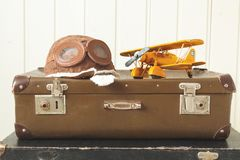 Helmet pilot and toy yellow metal plane Two old retro suitcases White wooden background Vintage tinting stock images