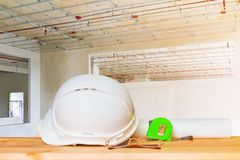 helmet plastic white with glasses, paper roll plan blueprint and measuring tape green on wood table in interior Construction site