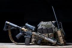 Helmet,rifle and military flak jacket. Assault rifle with sight,bulletproof vest,ammo and radio on dark background Stock Image