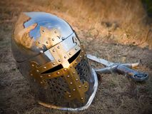 Helmet and sword on the grass after the battle stock photo