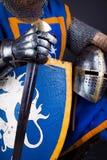Helmet, sword in hands Royalty Free Stock Image