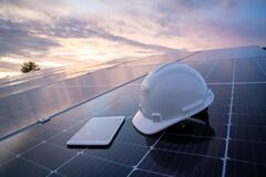 Free Helmet With Tablet On The Solar Panel For Working Solar Station Photovoltaic Panels, Science Solar Energy,engineer Working On Royalty Free Stock Photo - 219766825