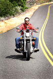 Helmetless Biker Rides Curvy Road. An unshaven bareheaded biker happily riding his bike in hill country on a curvy road wearing red plaid shirt and sunglasses Stock Photo