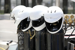 Helmets. A line of four white motorcycle helmets on posts royalty free stock photography