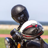 Crash Helmets on a Motorbike. Two helmets hanging on the mirrors of the motorcycle Royalty Free Stock Photo
