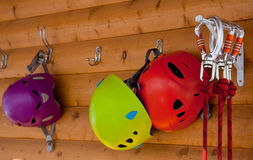 Helmets, safety carabiner. Helmets and harnesses carabiners hanging on the wooden wall Royalty Free Stock Photography