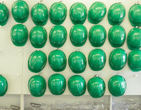 Helmets and Safety Goggles. A wall of green safety helmets and trays of safety goggles Royalty Free Stock Images