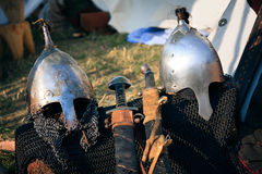Helmets and swords. Iron helmets circa IX-XII century, protecting a head, eyes and nose, for tournaments and battle combat Royalty Free Stock Images