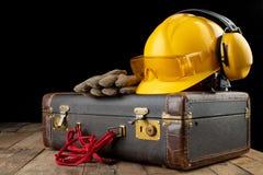 Helmschoenen en handschoenen op een reiskoffer Werkkledij op het reizen op een het werklijst die wordt voorbereid stock fotografie