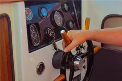Helmsman. The man`s hand holds the wooden steering wheel of the boat. Close-up of the dashboard. Management of water transport. Man at the helm Royalty Free Stock Photography