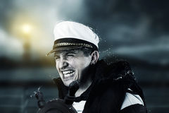 Helmsman with vest and cap struggle against storm in front of bl Stock Image