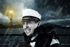 Helmsman with vest and cap struggle against storm. In front of the coast and light tower royalty free stock photo