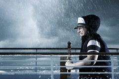 Helmsman with vest and cap struggle against storm in front of st royalty free stock photography