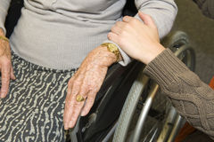 Help. A young hand touches the arm of an elder woman in a wheelchair Stock Photography
