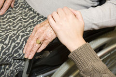 Help. A young hand touches the hand of an elder woman in a wheelchair Royalty Free Stock Photos