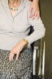 Help. A young hand touches the shoulder of an elder woman in a wheelchair Royalty Free Stock Photos