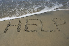 Help. Written in sand on beach Stock Images