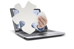 Help. A hand reaches out of a laptop with pieces of puzzle Stock Image