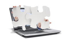 Help. A hand reaches out of a laptop with pieces of puzzle Royalty Free Stock Image
