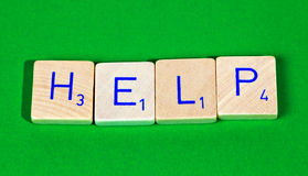 Help. Wooden letter blocks isolated on green background Royalty Free Stock Images