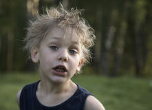 Help!. Crying dishevelled boy with wet hair and forest behind him Stock Photo