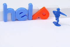 Help. A toy policeman running for help, with the world help in letters in the background Stock Photography