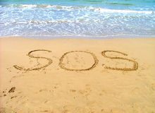 Help. Sos sign for help written in sand stock image