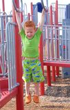Help!!. A young boy is hanging on the monkey bars in a playground Stock Photo