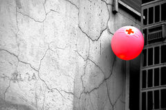 Help. Red balloon with red cross on it attached to the rough white wall Stock Photo