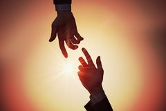 Help and assistance concept. Two hands are reaching each other at sunset stock photos