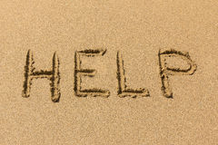 Help background. HELP - message written on the sandy beach Royalty Free Stock Photo