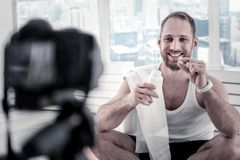 Cheerful male blogger recommending proteins. Help for body. Jolly vigorous male blogger smiling while demonstrating vitamins and recording video royalty free stock images