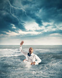 Help businessman falls. Businessman drowning in the sea and asks for help Stock Photo