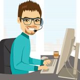 Help Call Center Operator. Young adult male help call center operator working on desk typing on computer keyboard and talking with headphones helpline concept royalty free illustration