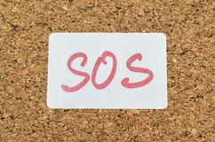 Help call SOS. Word SOS handwritten on a sticker pinned on a cork board stock photography