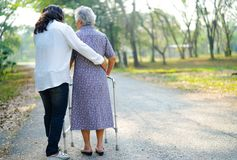 Help and care Asian senior or elderly old lady woman use walker with strong health while walking at park. Help and care Asian senior or elderly old lady women royalty free stock photos