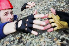 Help for climber. Climber in red helmet reach out for help Royalty Free Stock Photo