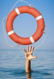 Help concept. Lifebuoy for drowning man's hand in. Lifebuoy for drowning man's hand in open sea or ocean water royalty free stock image