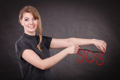Happy woman with sos sign. Help concept. Young blonde smiling woman with red sos symbol sign. Happy female helper offering support Royalty Free Stock Photography