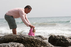 Help from Daddy. Father helping his daughter off the rocks stock photo