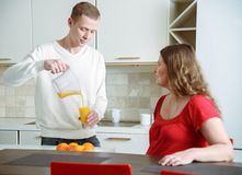 Help and devotion. Young couple at their home kitchen, husband giving orange juice to his pregnant wife stock photo