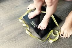 Help fat or obese child with toddler on weight scale, supervised by a parent stock images