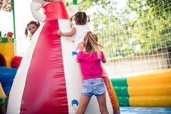 Help and fun. Three little girl playing together on playground royalty free stock image