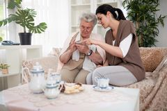 Help is always good. Old women holding smartphone and getting instruction of young woman stock photo