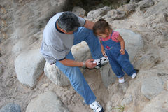 Help from grandpa. Grandfather helping grandaughter during hike stock photography