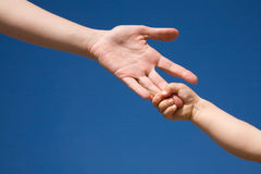 Help hand. The children's hand keeps for fingers of a mum's hand against the blue sky Royalty Free Stock Images