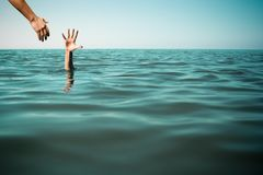 Help hand for drowning man life saving in sea or ocean. Stock Photo