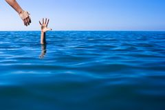 Help hand for drowning man life saving in sea or ocean. Royalty Free Stock Images
