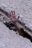 Help. Hand of a man caught in a crack in the asphalt Royalty Free Stock Photography